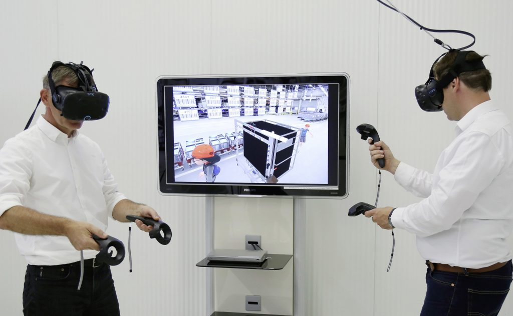 First Group VR applications for production & logistics:Mathias Synowski (left), Group Logistics, and Dennis Abmeier, Group IT, testing a new virtual reality application for production & logistics in the Volkswagen Group. Here, they are diving into the deceptively real world of virtual production reality with the HTC Vive headset.